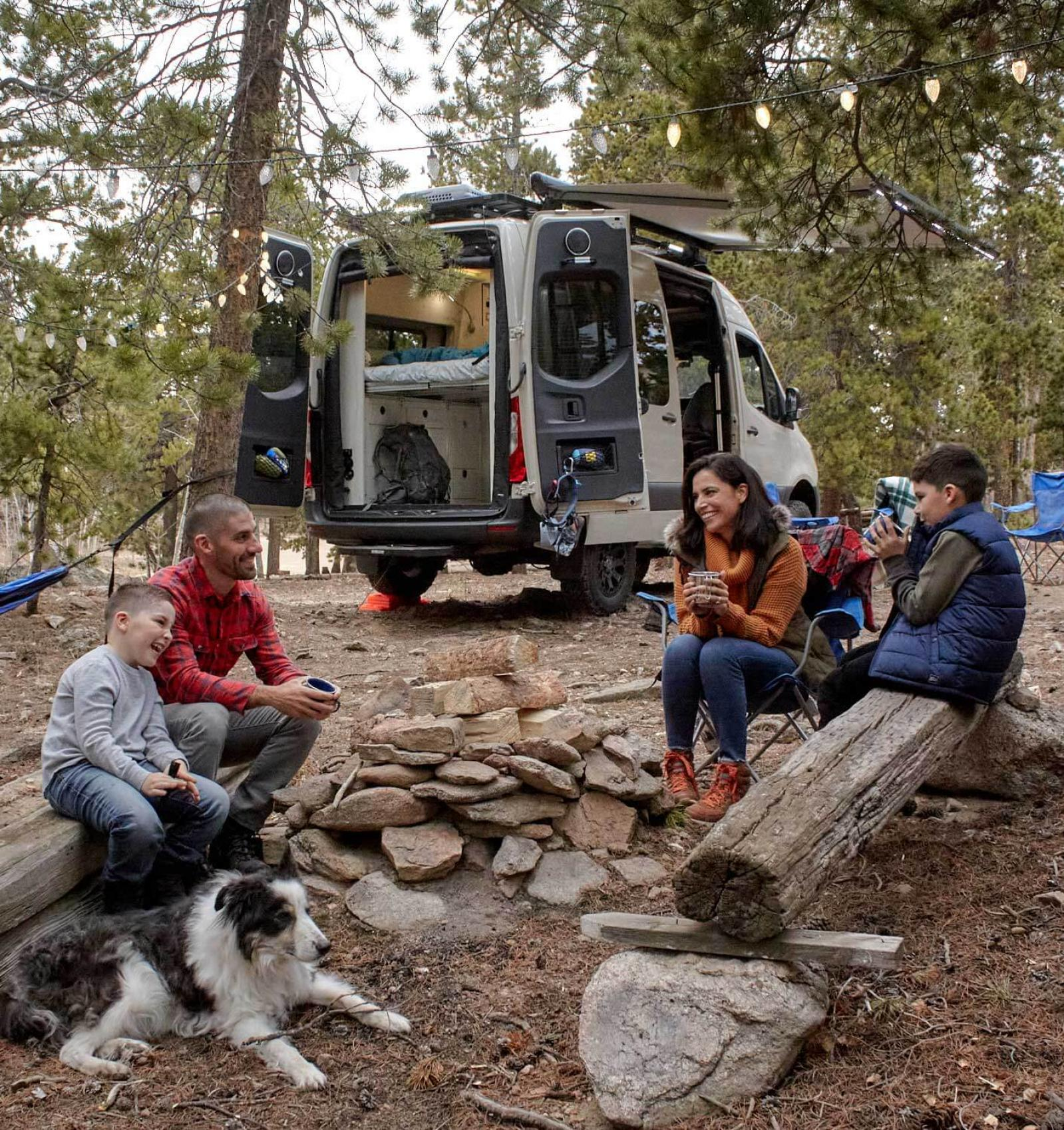 A family sitting outdoors in chairs in front of an Antero Adventure Van