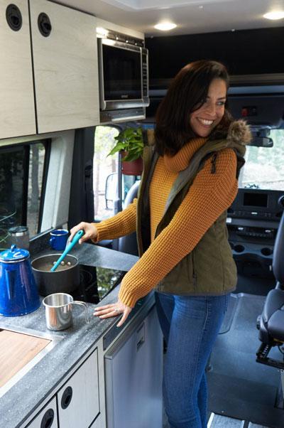 A woman using the kitchen inside an Antero Adventure Van