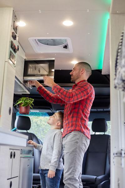 A man using the microwave inside an Antero Adventure Van