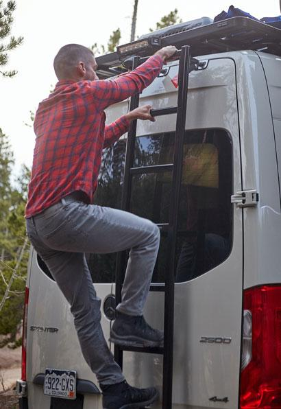 A man climbing up the ladder on the back of an Antero Adventure Van