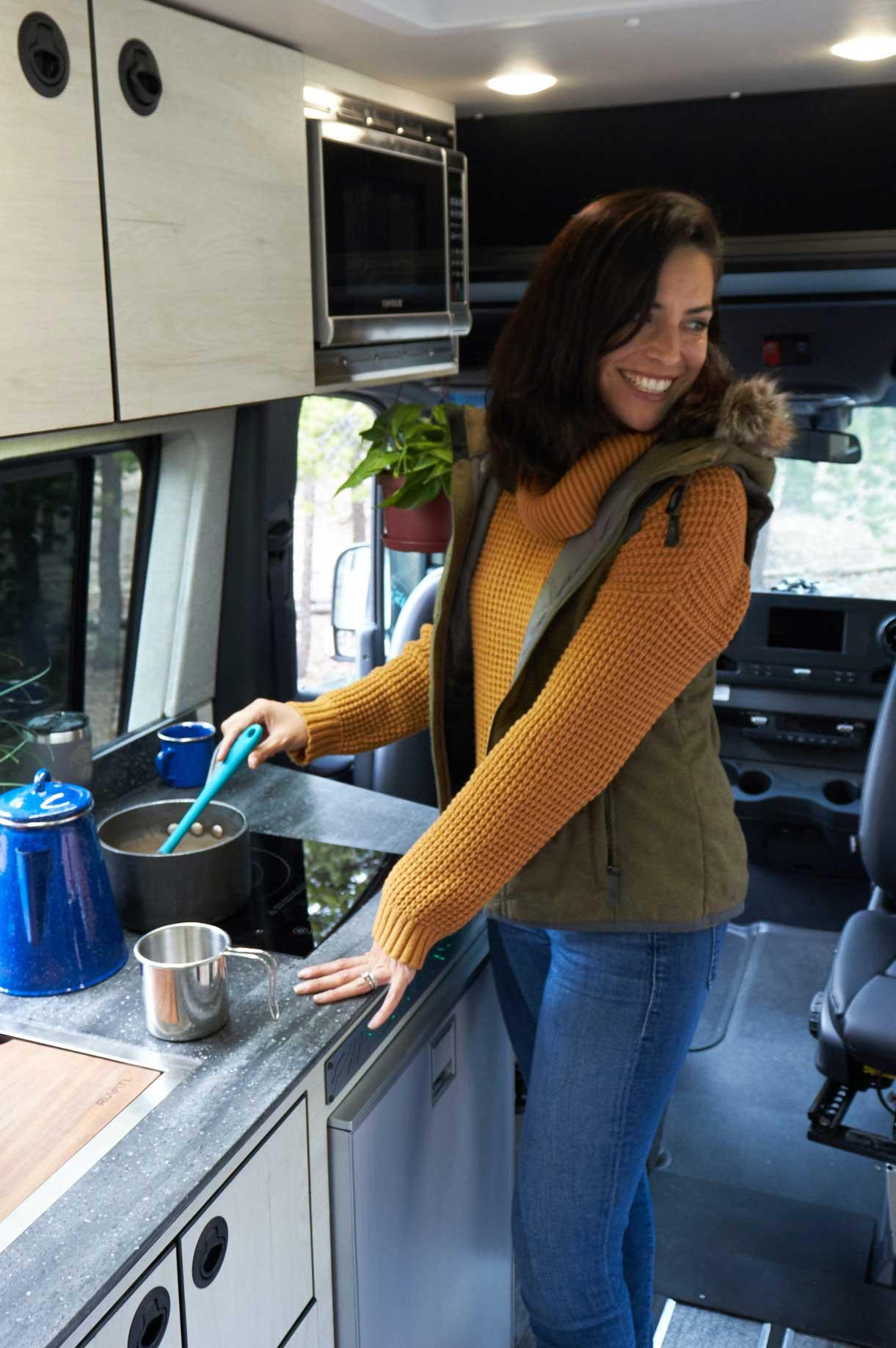 A woman using the kitchen inside a Summit Adventure Van