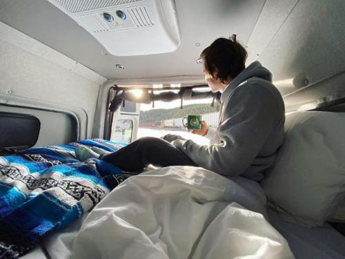 A person sitting on a bed in the back of a Summit Adventure Van