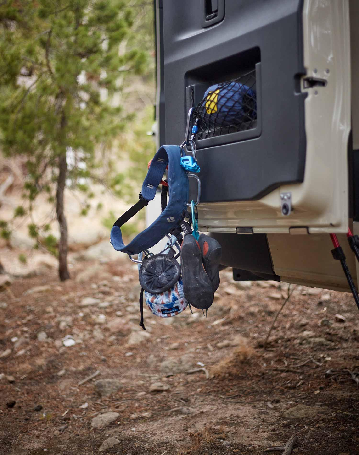 A climbing harness hanging from the back of a Summit Adventure Van