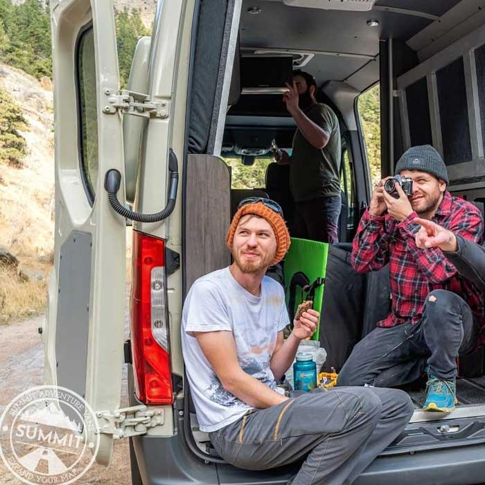 Three people hanging out in the back of a Summit Adventure Van, one taking a picture