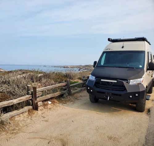 A Summit Adventure Van driving on a dirt road with a beach in the background