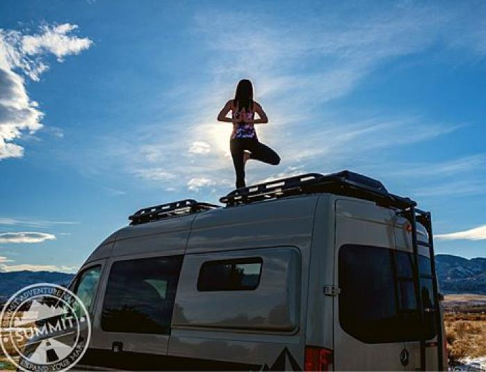 A person doing yoga on the top of a Summit Adventure Van